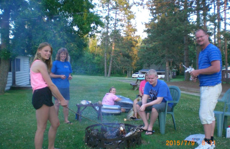 Family by campfire at Cedarwild Resort.