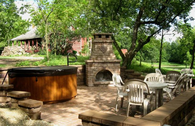 Fireside Patio at Red Cedar Lodge features a stone fireplace and large hot tub on a spacious patio for relaxing and entertaining.