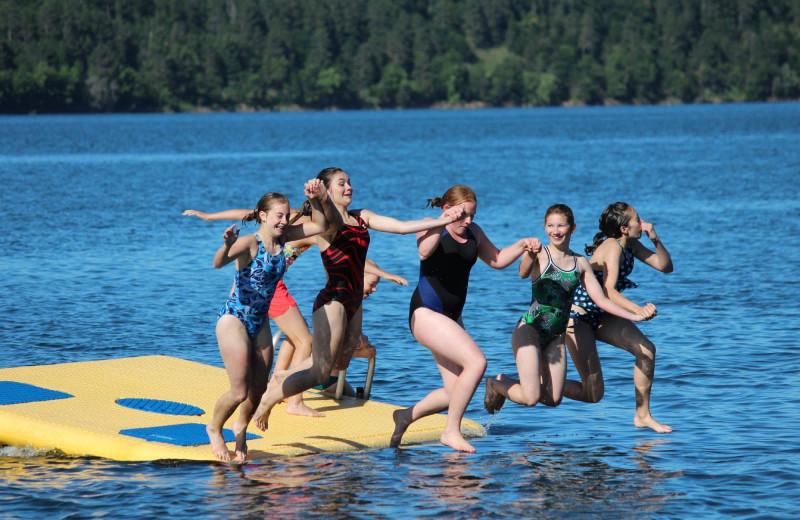 Kids jumping in lake at Auger's Pine View Resort.
