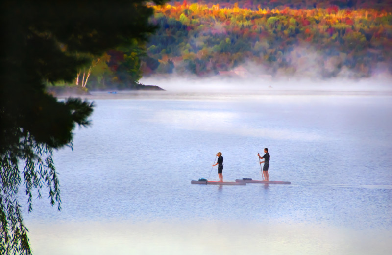 Spectacular peak fall foliage and pristine international Wallace Pond provide the perfect setting for stand-up paddle boarding of the sandy beach at Jackson's Lodge, Canaan, Vermont's Northeast Kingdom.
