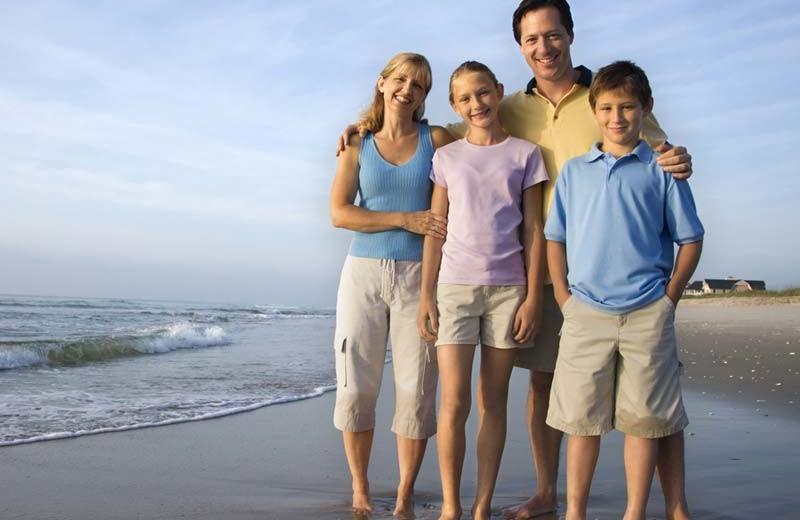 Family on beach at The Inn at English Meadows.