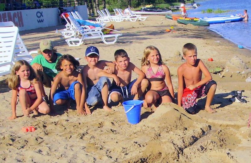 Family on beach at Hiawatha Beach Resort.