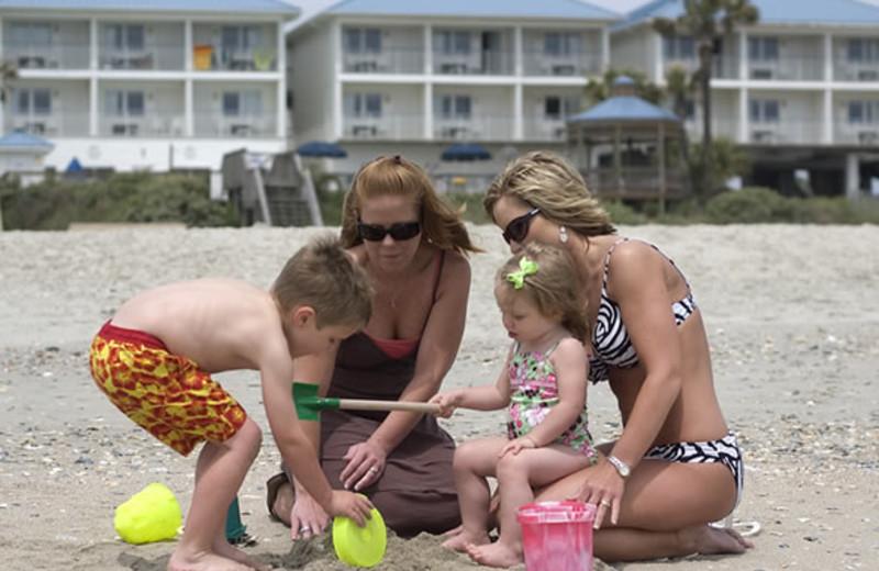 Family on beach at Ocean Isle Inn.