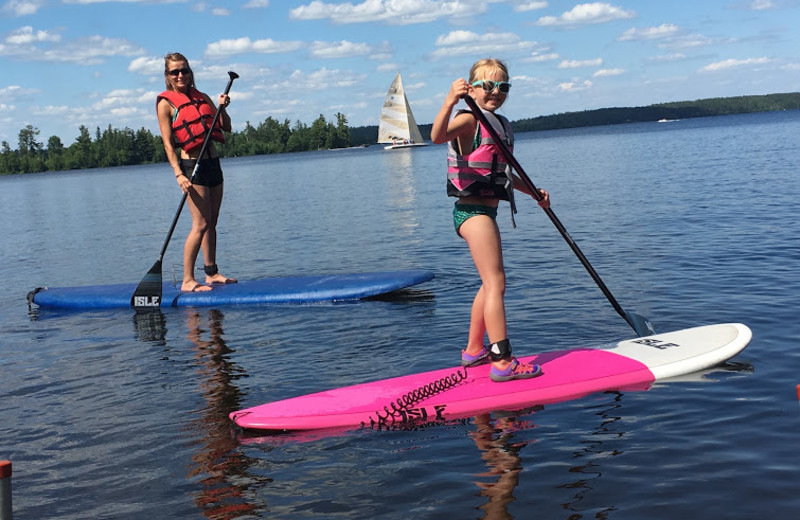 A mother and daughter paddle boards at Pehrson Lodge Resort.