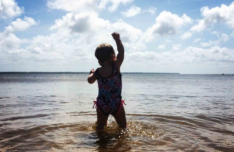 Child in water at Beach Realty & Construction.