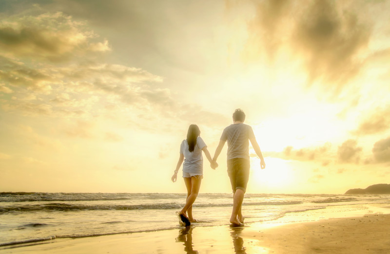 Couple walking on beach at CNE Vacation Rental.