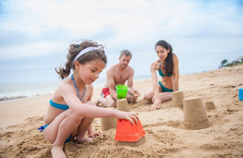 Family making sandcastles at Ocean Walk Hotel.