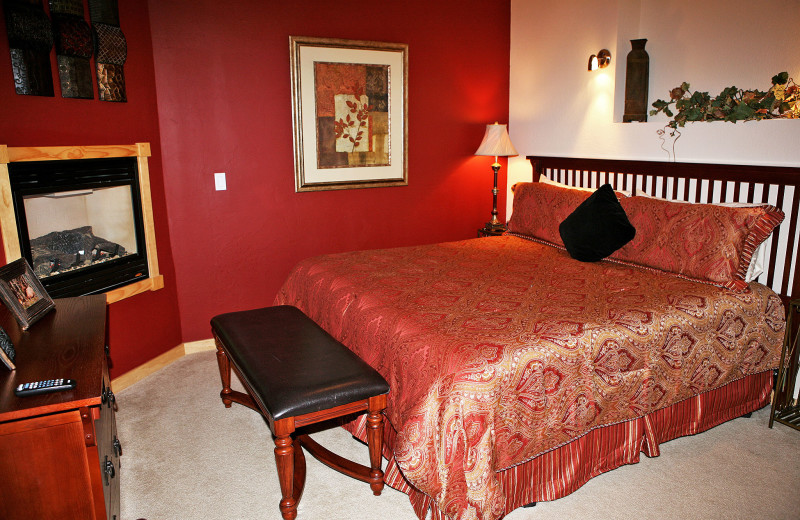 Vacation rental bedroom with fireplace at Marys Lake Vacation Condos.