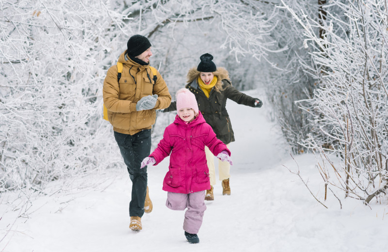 Family running through snow at GO-Cottage.