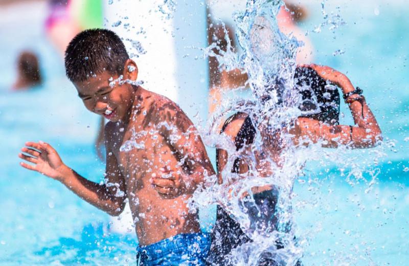 Kids splashing in pool at Great Blue Resorts- Vine Ridge Resort.