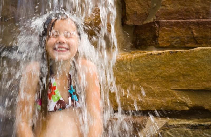 Kid under waterfall at Hyatt Regency Lost Pines Resort and Spa.