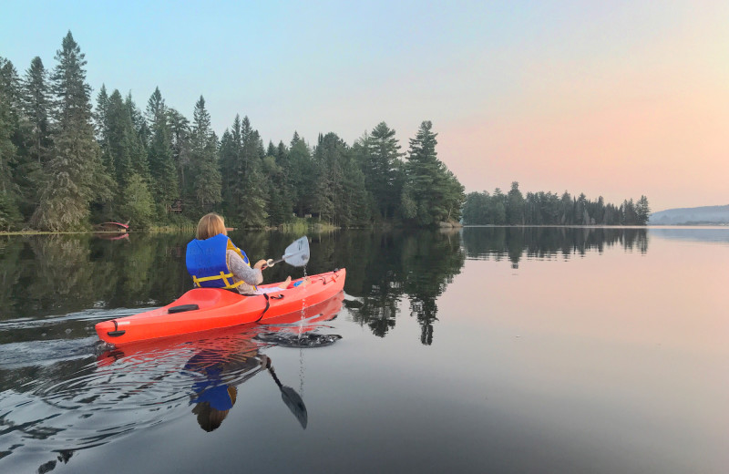 A guest heading out for a paddle after supper on a warm summer evening at Killarney Lodge in Algonquin Park