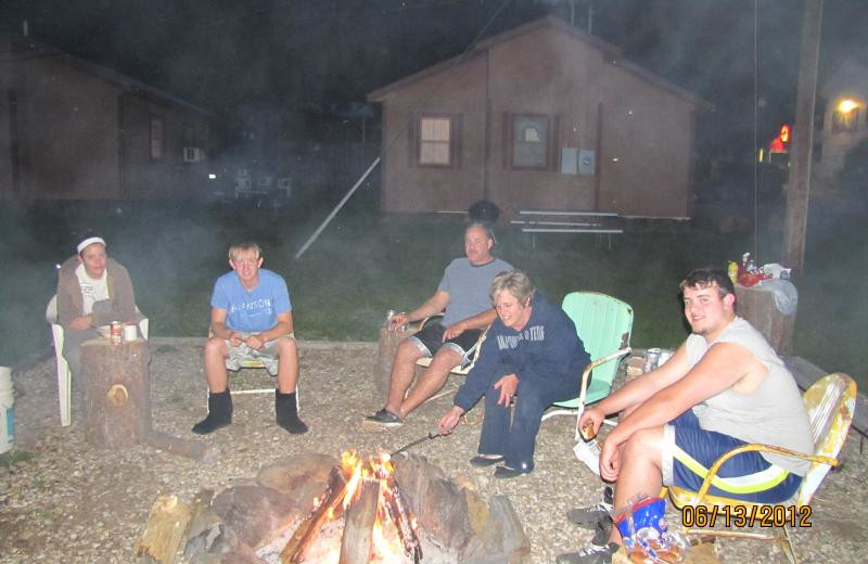 Family around campfire at Black Hills Cabins & Motel at Quail's Crossing.