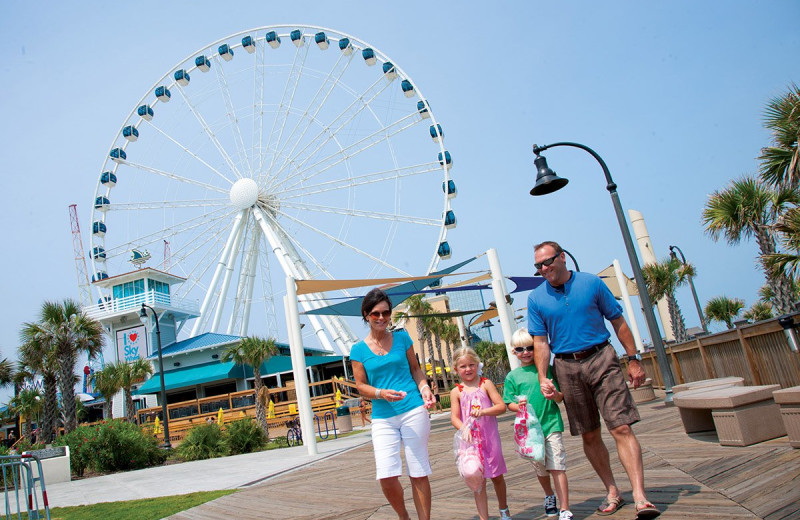 Family on boardwalk at The Strand Resort Myrtle Beach.