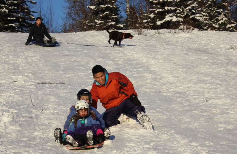 Family sledding at Salmon Catcher Lodge.