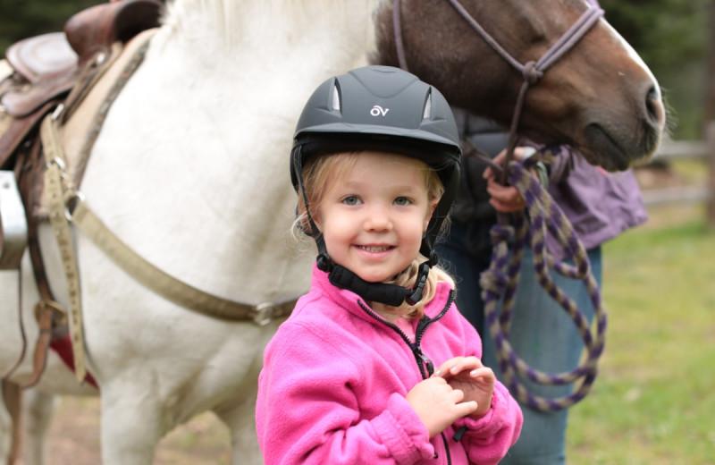 Kid and horse at Tumbling River Ranch.