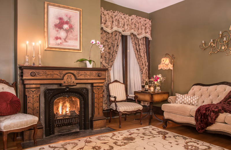 Part of the two-room Penfield Suite, the parlor boasts beautiful wood carvings on the fireplace.  It has a sofa, two wing back sitting chairs & tables to relax in your private haven.
