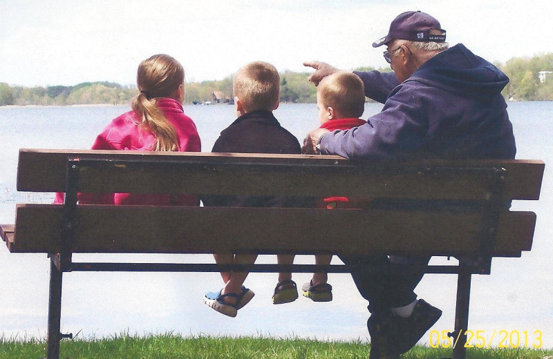 Family on bench by lake at Seclusion Point Campground.
