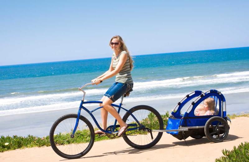 Biking along beach at Sanibel Vacations.
