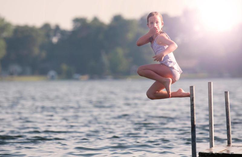 Kid jumping in lake at Great Blue Resorts- Shamrock Bay Resort.