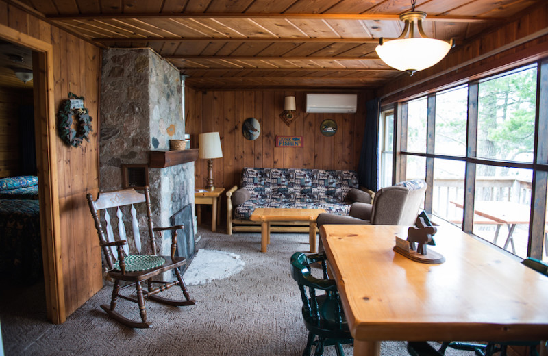 Northern Lights cabin's living and dining room with large picture windows and wood burning fireplace.