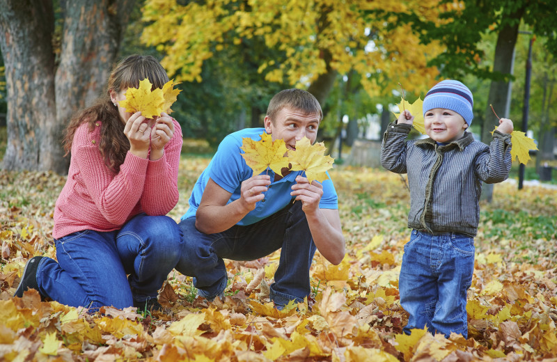 Family playing in leaves at Patterson Kaye Resort.