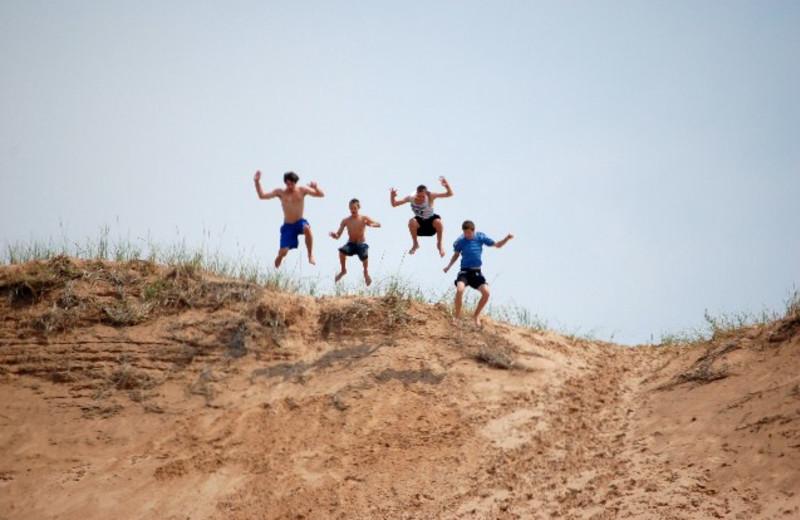 Kids jumping on beach at Chimney Corners Resort.