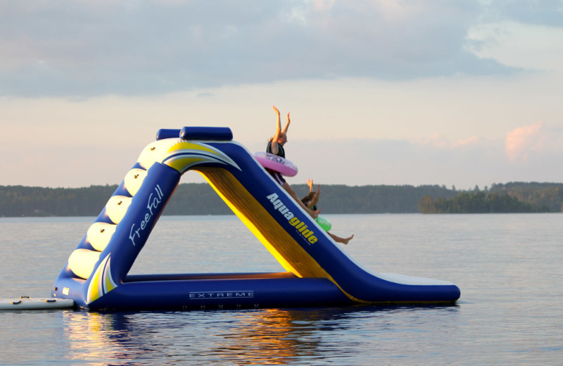 Blow up water slide with a 2 girls sliding down.