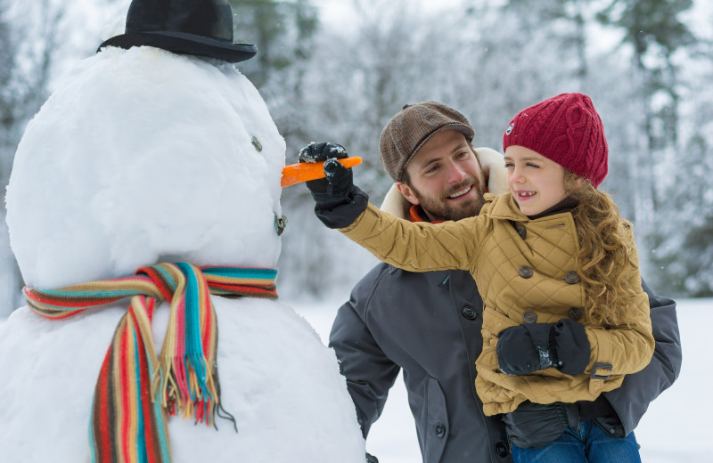 Family making a snowman at Fairmont Le Chateau Montebello.