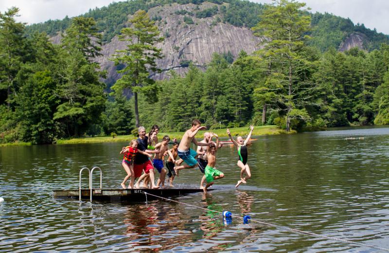Kids jumping in lake at High Hampton Resort.