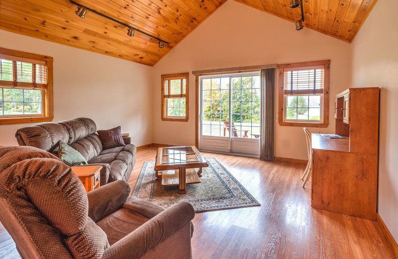 Meticulously clean country-style decorative chalet living room graced with cathedral ceiling, fully furnished kitchen and lake views at Jackson's Lodge and Log Cabin Village