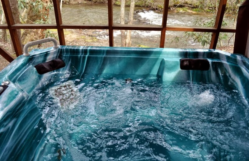 Deck jacuzzi at Cuddle Up Cabin Rentals.