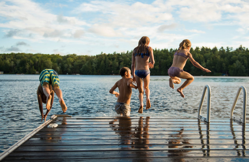 Kids jumping in lake near Blue Beaver Luxury Cabins.