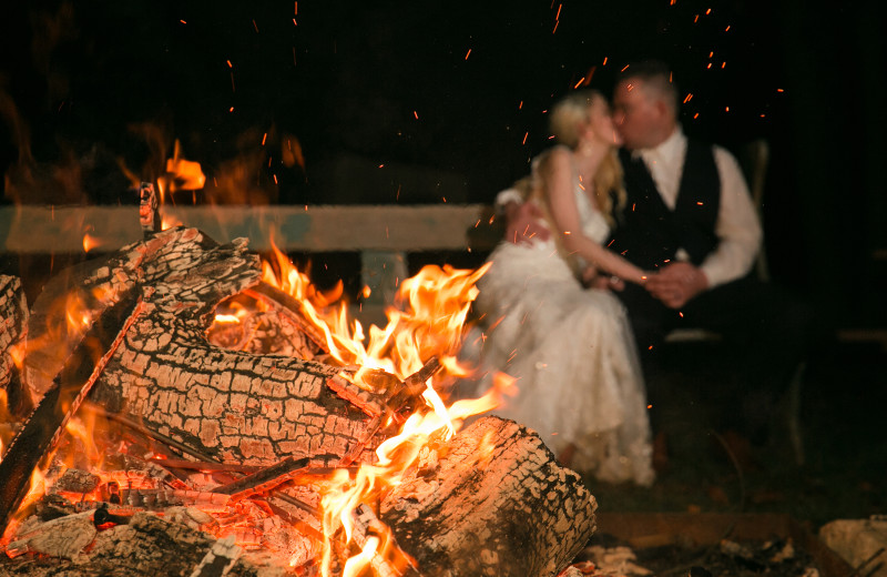 Couple by bonfire at Arrow Park Lake and Lodge.