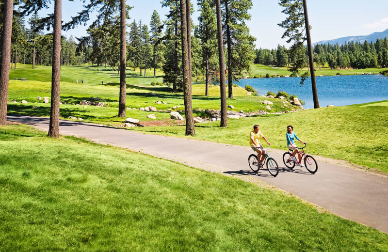 Couple biking on golf course at Suncadia Resort.