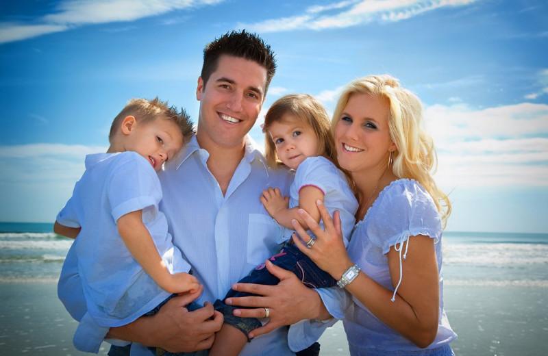 Family on beach at Gulf Winds Resort Condominiums.