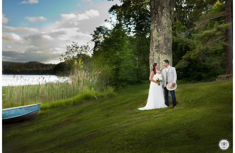 Wedding couple kissing by lake at Twin Pines Resort.