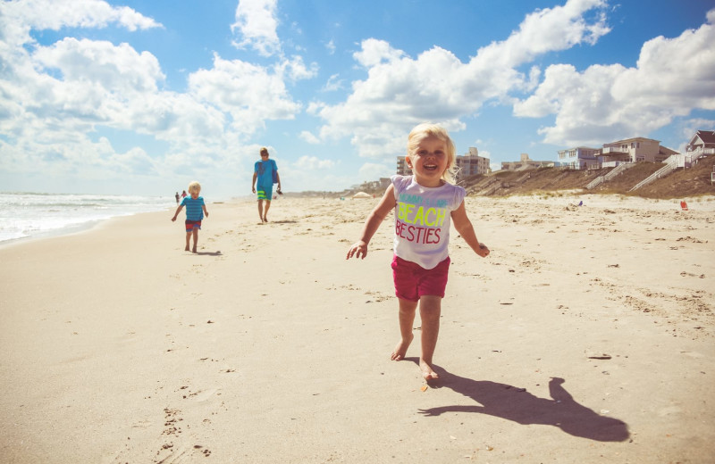 Kid running on beach at Realty World - First Coast Realty.