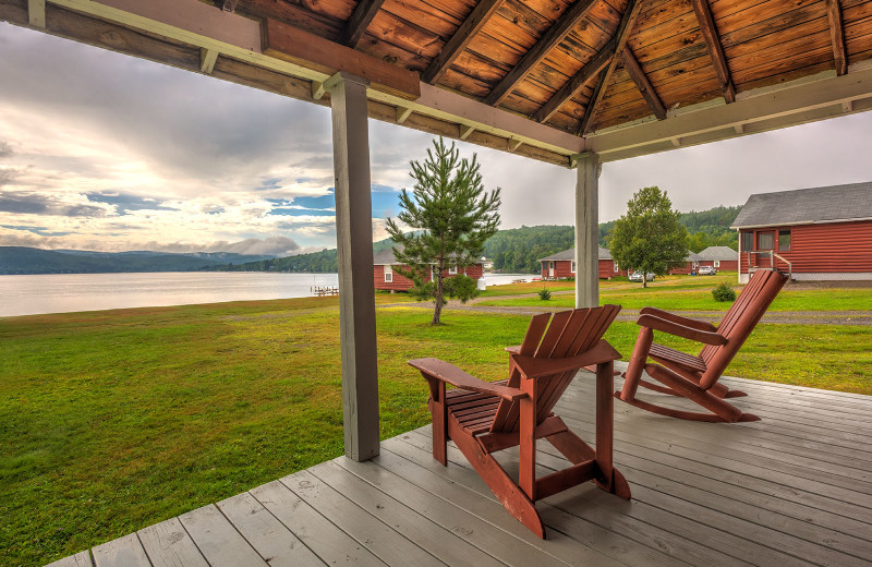 Meticulously clean country-style decorative rustic cabin porch at Jackson's Lodge and Log Cabin Village on international Lake Wallace, Canaan, Vermont.