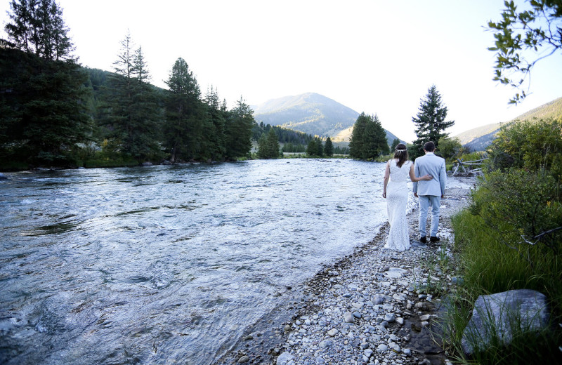 Wedding couple by river at 320 Guest Ranch.