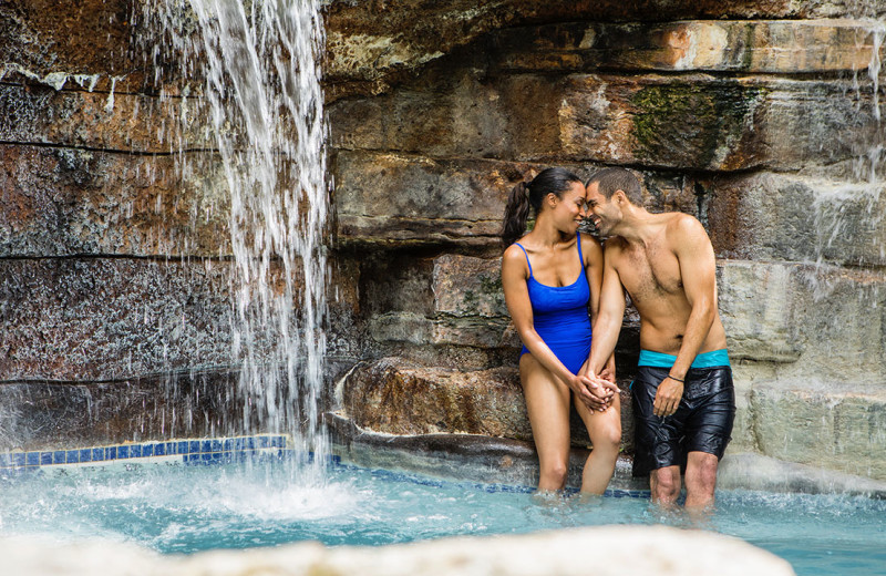 Couple by water fall at Hyatt Regency Hill Country Resort and Spa.