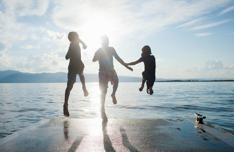 Family jumping in lake at Averill's Flathead Lake Lodge.