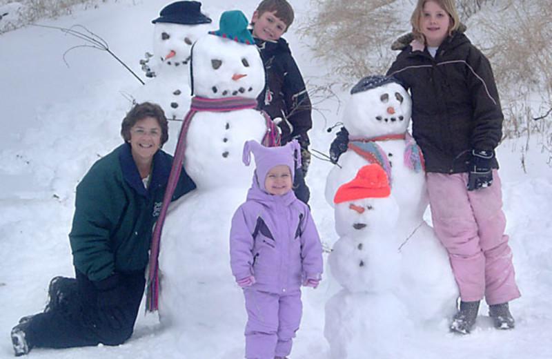 Family building snowmen at Brophy Lake Resort.