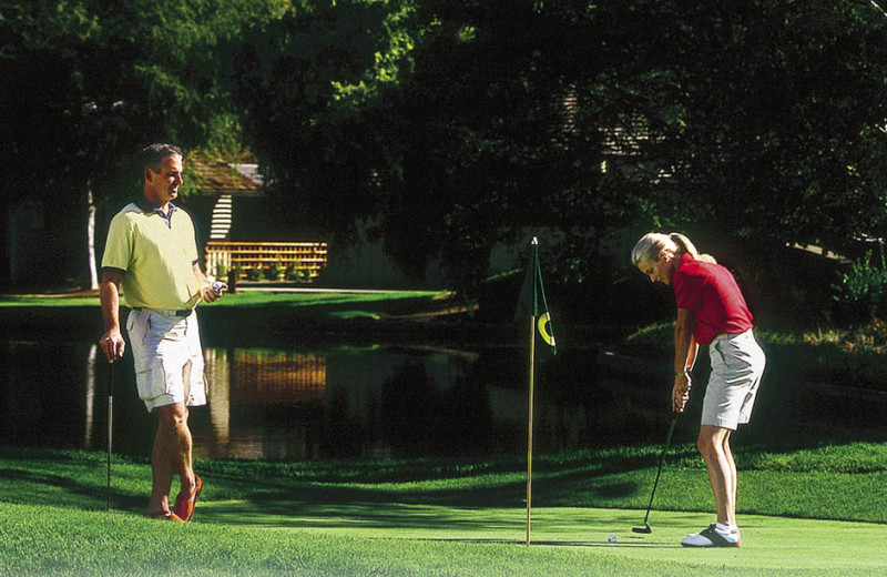 Couple playing golf at Quail Lodge Resort.