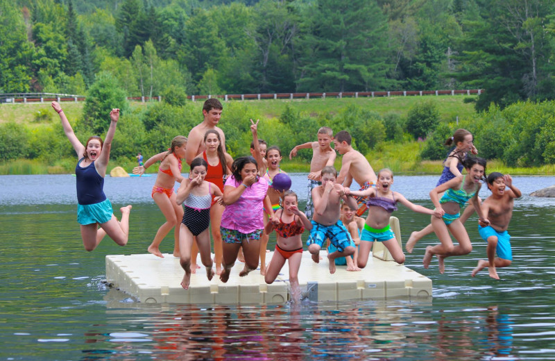Family jumping in lake at Waterville Valley Resort Association.