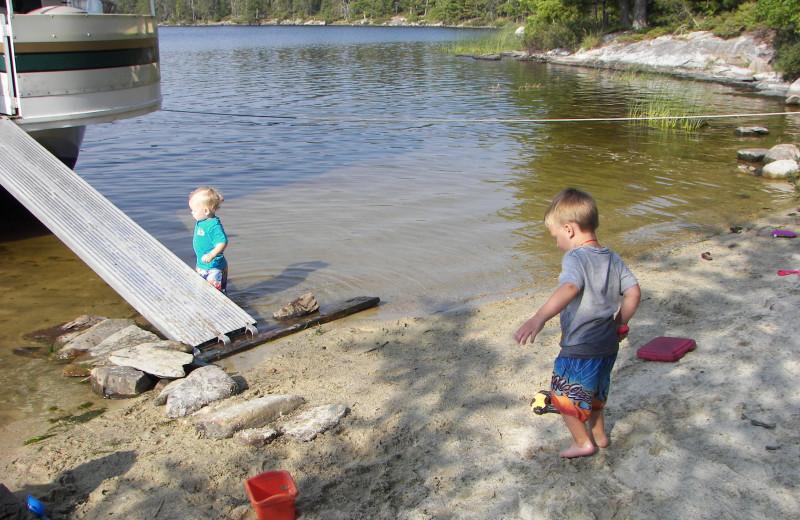 Family by the lake at Rainy Lake Houseboats.