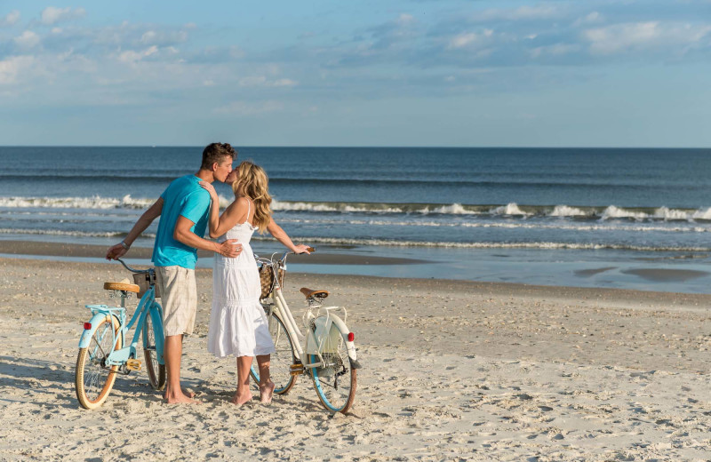 Couple with bikes on beach at The Winds Resort Beach Club.