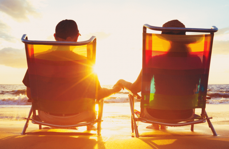 Couple on beach holding hands at ACP Vacation Rentals.
