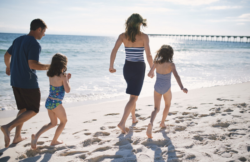 Family walking on beach at Sterling Resorts.
