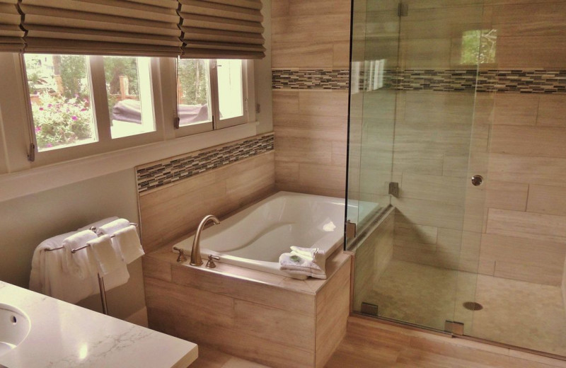 Soaker tub and walk-in shower at Huff House Inn & Cabins